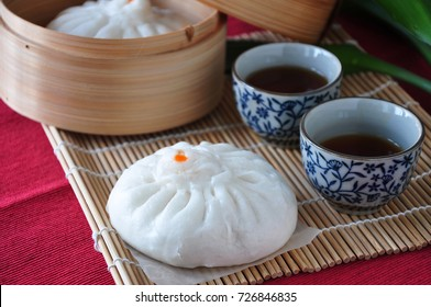 Close up Siopao Chinese steamed pork bun with cup of hot tea on bamboo mat background