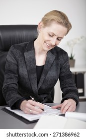 Close up Sitting Happy Businesswoman in Black Office Attire Writing on a Paper at her Desk.