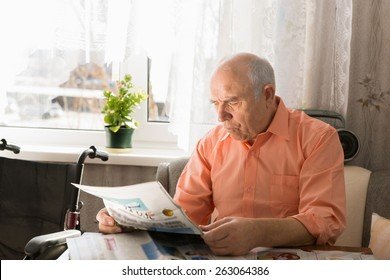 Close up Sitting Pensioner Reading News on Tabloid While Resting at the Living Area Near the Window.