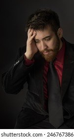 Close up Sitting Worried Goatee Man in Formal Suit, Putting his Hand on his Face. Captured on Gray Background