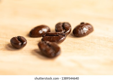 Close up of six roasted coffee beans
