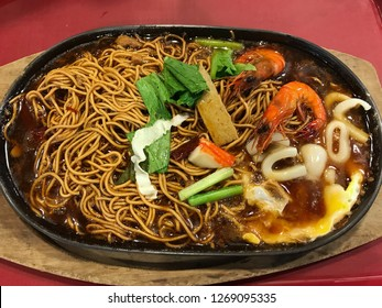 Close up of Sizzling noodle in cast iron serving platters with egg, seafood, vegetables, tofu, and noodles.