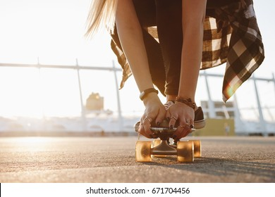 Close up of skater's legs in black sneakers and hands with rings on a skate board