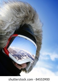 Close up of the ski goggles of a man with the reflection of snowed mountains
