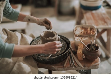 Close up of skilled craftswoman removing part of clay while making pot in pottery workshop