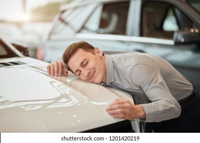 Close up of skillful male sales rep hugging a new car with closed eyes at dealership, displays all his appearance to the potential customers that this car is a special one.
