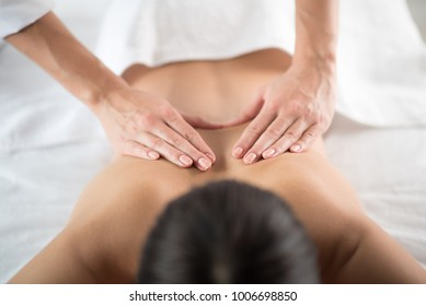 Close up of skillful masseuse hands massaging back of young girl. Health concept