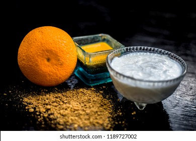 Close up of skin whitening method or remedy i.e. raw orange dried skin powder well mixed with yogurt or curd on wooden surface in a transparent glass cup with raw orange.