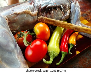 Close up of a slaughtered outdoor rabit with fresh organic vegetables on a wooden surface including red and yellow peppers and bright red tomatoes