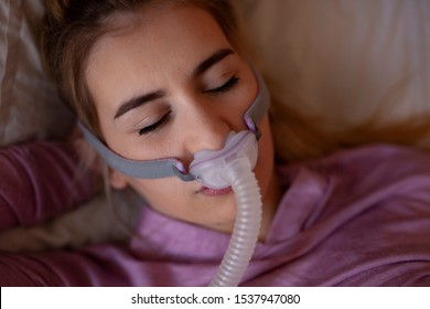 Close up of sleeping with cpap machine in purple, pink female