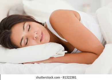 close up of a sleeping gorgeous woman lying under sheet in bedroom