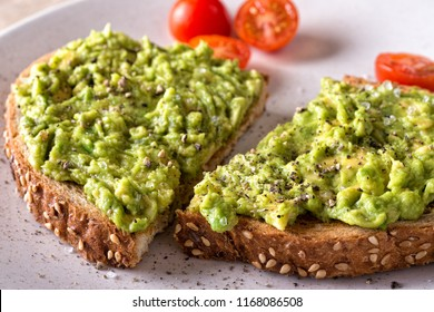 Close up of a slice of delicious avocado toast with sliced tomato.