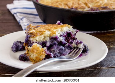 Close up of slice of fresh baked blueberry cobbler sitting on white plate with fork
