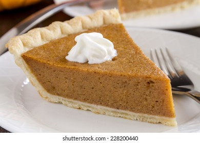 Close up of slice of homemade pumpkin pie with whipped cream sitting on white plate with fork