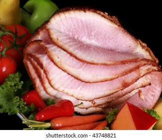 Close up of a sliced ham on black background