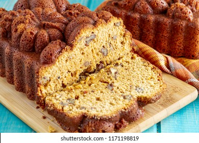 Close up of sliced loaf of pecan pumpkin bread sitting on wooden cutting board with full loaf in background on blue wooden table