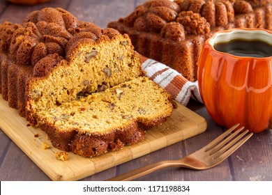 Close up of sliced loaf of pecan pumpkin bread sitting on wooden cutting board with full loaf in background and cup of coffee in pumpkin mug