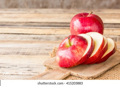 Close up of a sliced red apple on a wooden table.