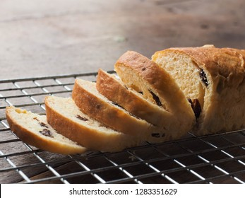 Close up slices of raisin bread loaf on wood table