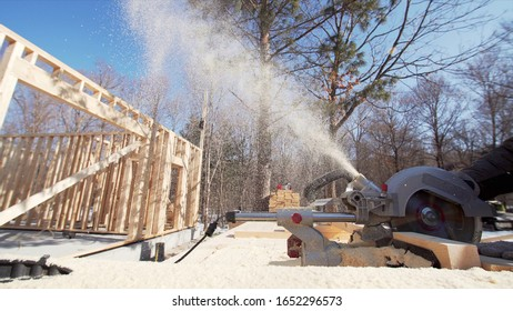Close sliding view of worker in sunglasses sawing wooden plank with miter saw. Frame house building. Sunny day. Forest is on the background