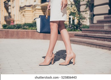 Close up of slim legs of woman wearing high heel shoes.
