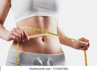 Close up of slim woman measuring her waist's size with tape measure. Isolated on white background.