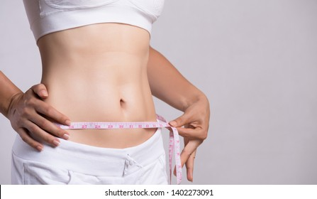 Close up slim young woman measuring her thin waist with a tape measure. Healthcare and woman diet lifestyle concept to reduce belly and shape up healthy stomach muscle.