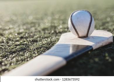 Close up of sliotar on top of hurl on ground