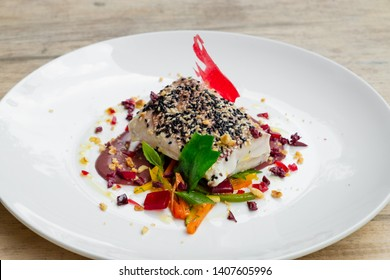 close up of a slow cooked , sous vide , tuna loin with black and white sesame crust, olive sauce, mixed vegetable and wine gelatine , white plate , natural light food photography, chef table inspired