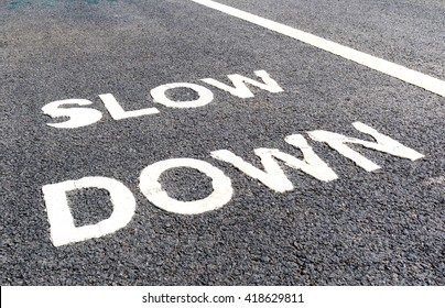 Close up slow down marking on street, for warning the drivers to reduce speed.