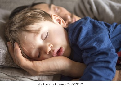 close up of a small boy fallen asleep on the couch with his father