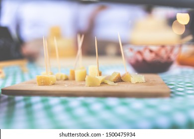 Close up of small cheese sample pieces with toothpicks on wooden cutting board.