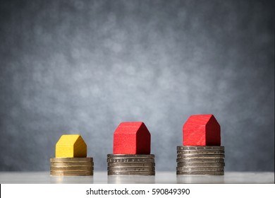 Close up of small different size wooden houses on top of stack of coins. Building costs planning concept.