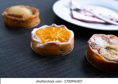 Nahaufnahme kleiner, französischer Zwiebeln mit Früchten und Zuckerpulver auf dunklem Hintergrund mit Teller und Gabel hinter
