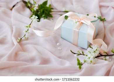 Close up of a small gift wrapped with pink ribbon. A small gift on a pink background with flowering branches. Shallow depth of field with focus on a small box. place for inscription