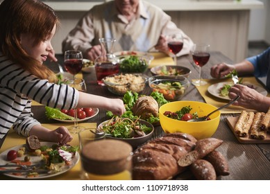 Close up of small girl sitting at table with family. She is bending to reach salad and put it into plate. Child is eating wholesome dishes looking concentrated