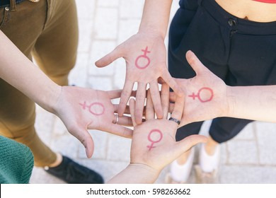 close up of small group of four women with the symbol of feminism written on her hands