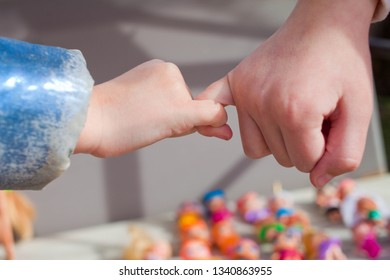 Close up of small kids reconcile after fight making pinky promise, children make peace with hand gesture joining pinkies swear not to argue or quarrel, siblings become friends. Friendship concept