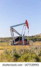 Close up of a small oil pump jack in the farmers field. Turner Valley, Alberta, Canada.