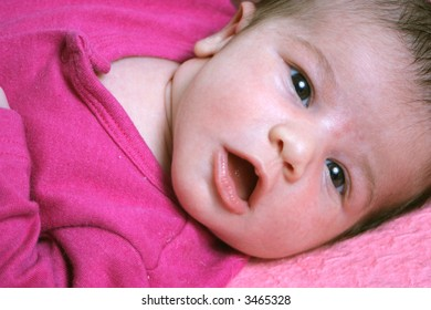 close up of a small one week old newborn baby on a pink background