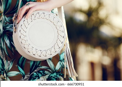 Close up of small round stylish bag. Elegant, trendy summer outfit. Fashionable woman posing in street. Model wearing green dress with tropical print. Female fashion concept. Copy space for text