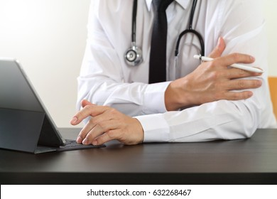 close up of smart medical doctor working with digital tablet computer and stylus pen and stethoscope on dark wooden desk