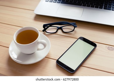 Close up of a smart phone, green tea and glasses on a wooden table