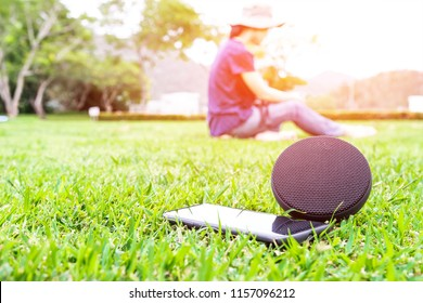 Close up smart phone and speaker on the green lawn floor with women listening to music in Mountain view, holiday concept