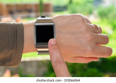 Close up of a smartwatch and an index finger as a concept of wearable technology