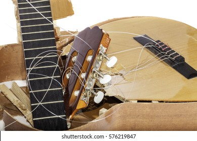 Close up of a smashed acoustic guitar broken in pieces.