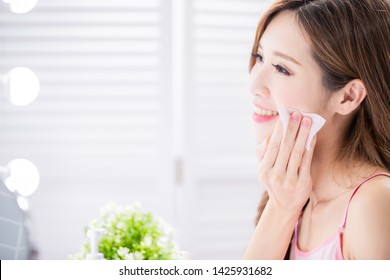 Close up of smile asian beauty woman use cleansing cotton on her face and look mirror