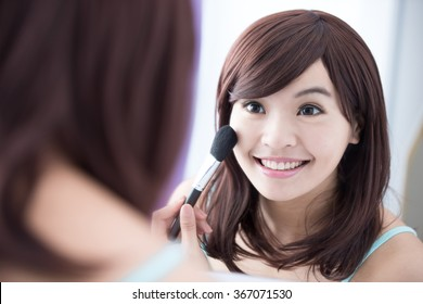 Close up of Smile woman with makeup brushes near face and look mirror. asian beauty