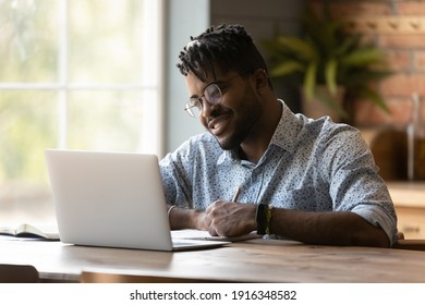 Close up smiling African American man wearing glasses using laptop, writing, taking notes, student watching webinar, studying online, looking at computer screen, sitting at wooden desk at home