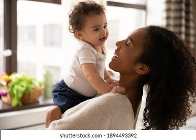 Close up smiling African American woman hugging adorable little daughter, standing at home, beautiful young mum holding cute toddler girl, enjoying tender moment together, childcare concept